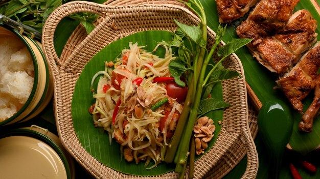 Thai-food-papaya-salat somtum mit gegrilltem hühnchen im thailändischen stil und klebrigem reis von oben