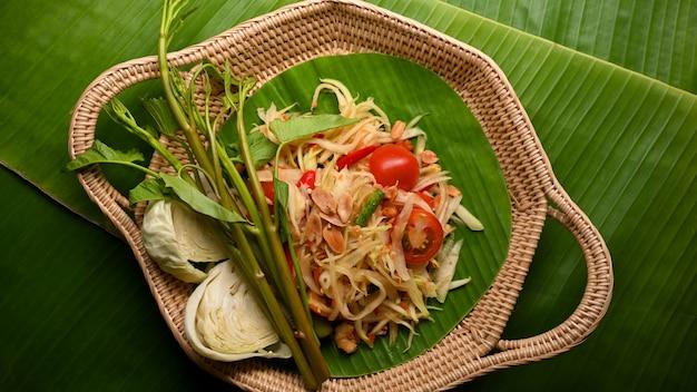 Thai-food-papaya-salat somtum mit gemüse auf weidentablett auf bananenblättern-hintergrund