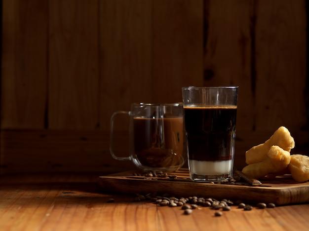 Thai-frühstück mit glas und tasse kaffee und frittierten teigstangen