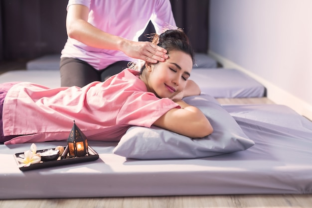 Thai-kopfmassage auf dem bett mit kerze und plumeria-blume im spa-salon