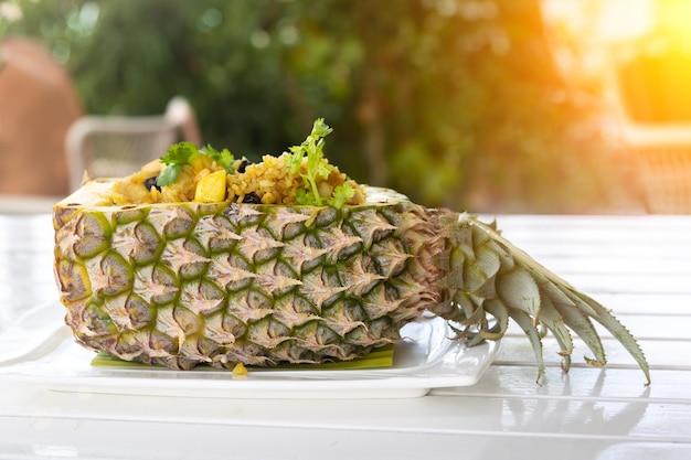 Thai-reis mit hühnchen in ananasplatte mit gemüse auf dem holztisch horizontale seitenansicht