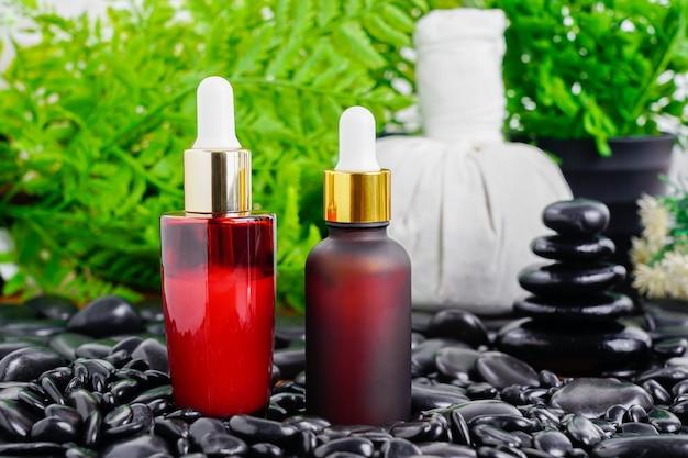 Thai spa massageeinstellung mit rotem serumölflaschentropfenmodell oder ätherischem öl auf schwarzem stein