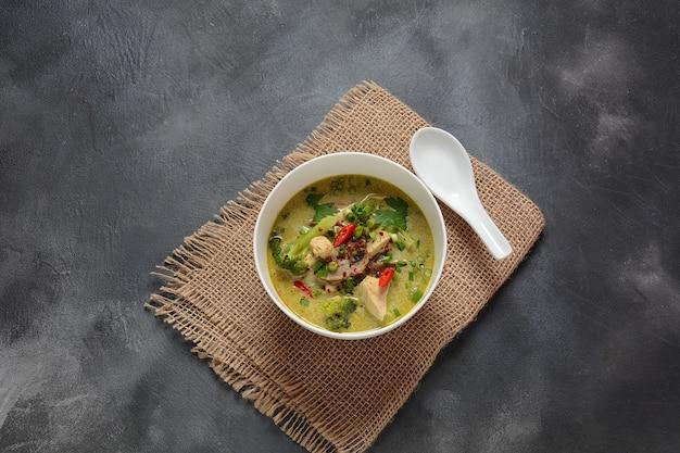 Thai spicy green curry hühnersuppe mit kokosmilch, pilzen und brokkoli.