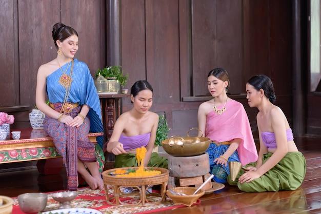 Thailänder machen thailändisches dessert im thailändischen kostüm