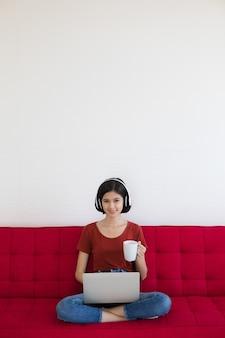 Thailändisch-deutsches süßes mädchen des halben rennens, das kopfhörer hält, der weiße kaffeetasse sitzt, die auf rotem sofa mit geschäftsgraph und diagramm sitzt und laptop-notebook-computerarbeit von zu hause mit glücksgefühl verwendet.