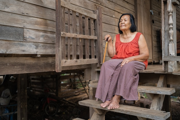 Thailändische ältere frau im ärmellosen kragen mit rundem hals, der einsam im alten hölzernen haus sitzt