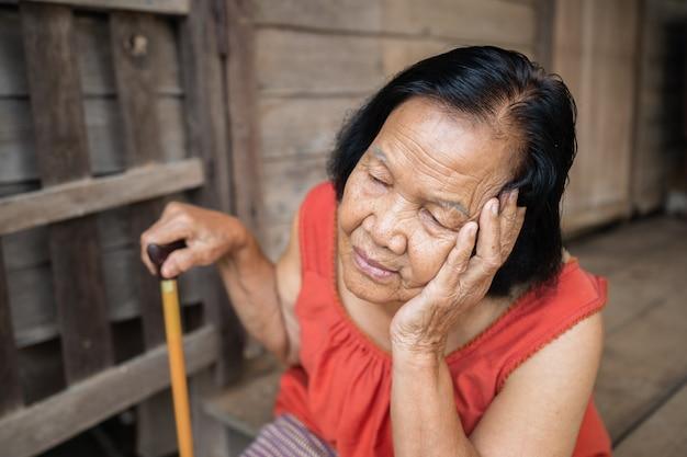 Thailändische ältere frau im ärmellosen rundhalskragen mit kopfschmerzen und besorgtem gestresstem gesicht im alten hölzernen haus