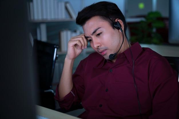 Thailändische asiatische callcenter-geschäftsleute bekommen kopfschmerzen und migräne, wenn sie spät in der nacht arbeiten