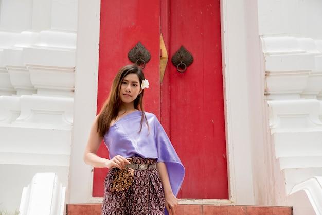 Thailändische asiatische höfliche frau mit lächelngesicht im traditionellen kostüm von thailand