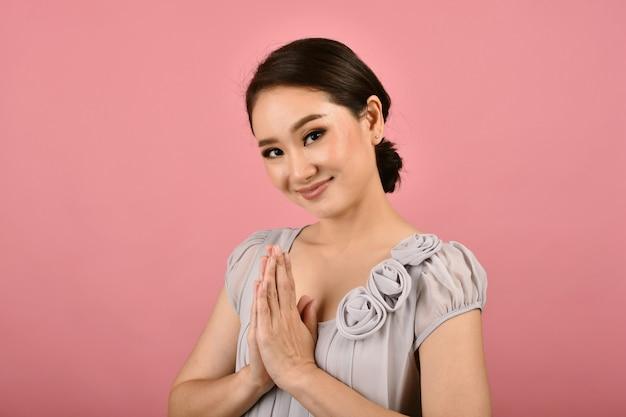 Thailändische asiatische lächelnde frau zahlen respekt mit wai-zeichen