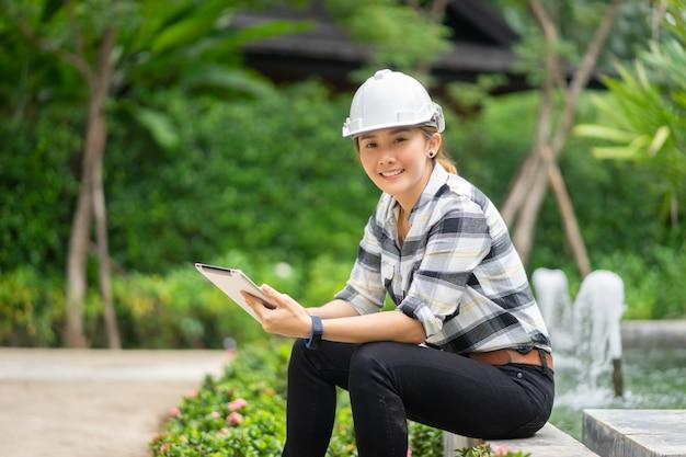 Thailändische asiatische weibliche technik, die mit einem tablettenlaptop in kläranlage arbeitet