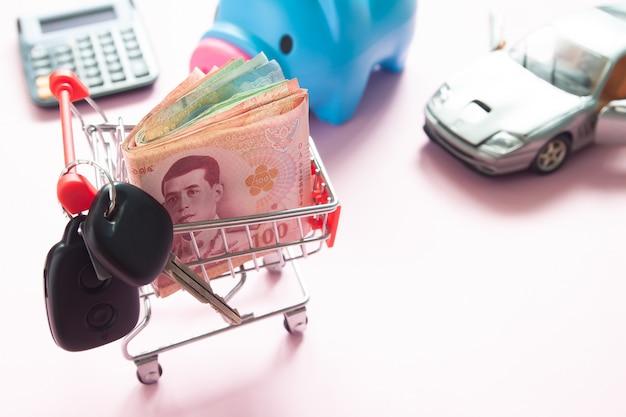 Thailändische banknoten im einkaufswagen, schlüssel, auto, sparschwein mit taschenrechner auf rosa hintergrund