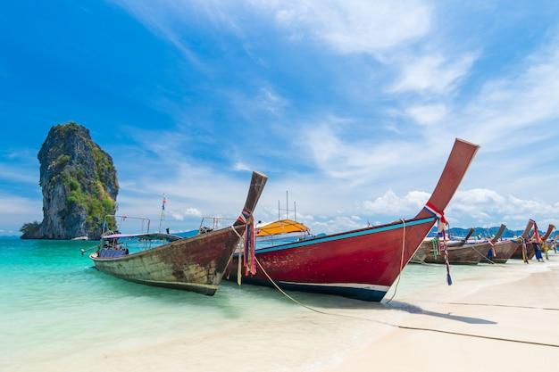Thailändische boote des langen schwanzes auf dem strand mit schöner insel
