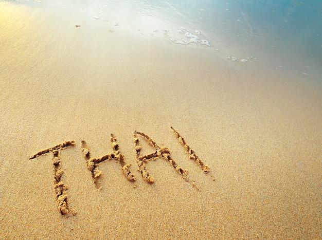 Thailändische buchstaben handgeschrieben im sand am strand