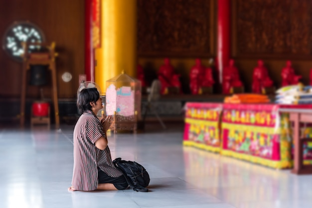 Thailändische buddhismusleute im buddhistischen beten für wohltätigkeitsanbetung zu buddha am chinesischen tempel unter der schirmherrschaft