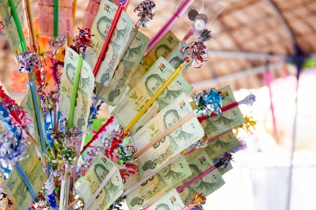 Thailändische buddhisten machen einen verdienst mit banknoten im songkran festival. songkran festival ist das traditionelle neujahrsfest in thailand.