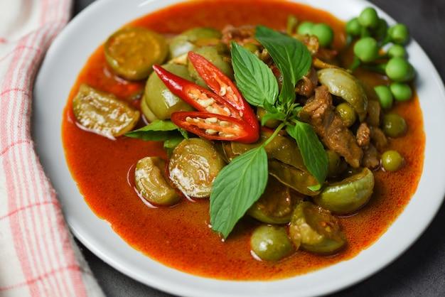 Thailändische curry-suppe auf weißem teller - asiatisches essen der roten curry-schweinefleischküche auf der tischwand