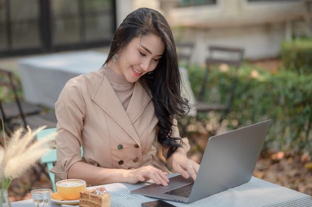 Thailändische designergeschäftsmänner, die an laptop über dem internet arbeitend mit kuchen und kaffee zum frühstück im garten sitzen