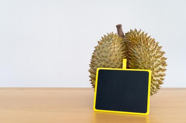 Thailändische durianfrucht auf dem holztisch mit dem leeren abschluss des schwarzen brettes herauf hintergrund