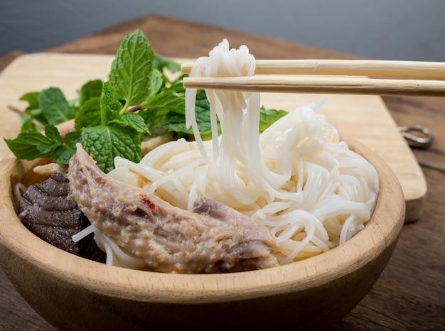 Thailändische fadennudeln mit curry und gemüse in der holzschale