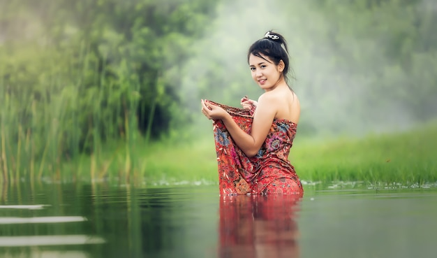 Thailändische frau, die im fluss badet