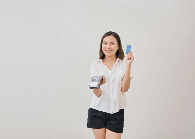 Thailändische frau, die kreditkarte für zahlung darstellt