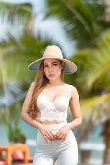 Thailändische frau, die weißes oberteil, weiße hosen und hosen im strand trägt