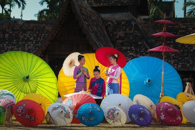 Thailändische frau im traditionellen kostüm (lanna-kulturart) mit schöner malerei thailands