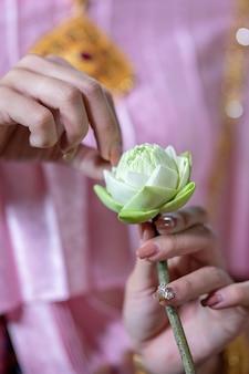 Thailändische frauen in traditioneller thailändischer kleidung schmücken blumen.