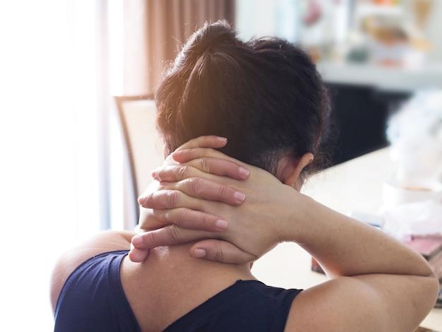 Thailändische frauen mit kopfschmerzen und nackenschmerzen verwenden eine handmassage am hinterkopf, um die muskeln zu entspannen.