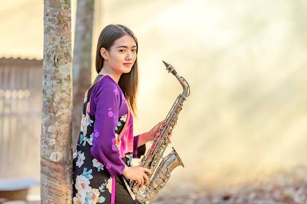 Thailändische frauen üben saxophon nach der schule, nach der schule, nachdem ich mein studium beendet habe