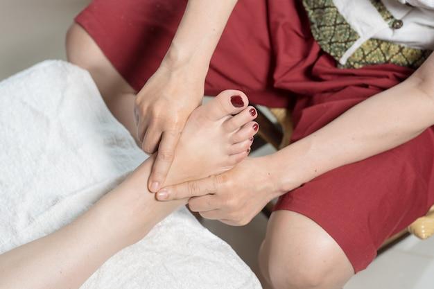 Thailändische frauenfußmassage und -badekurort mit junger frau die massage in thailand