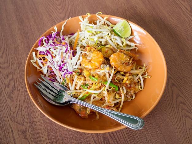Thailändische fried noodles mit garnele und gemüse, auflage thailändisch auf einem holztisch