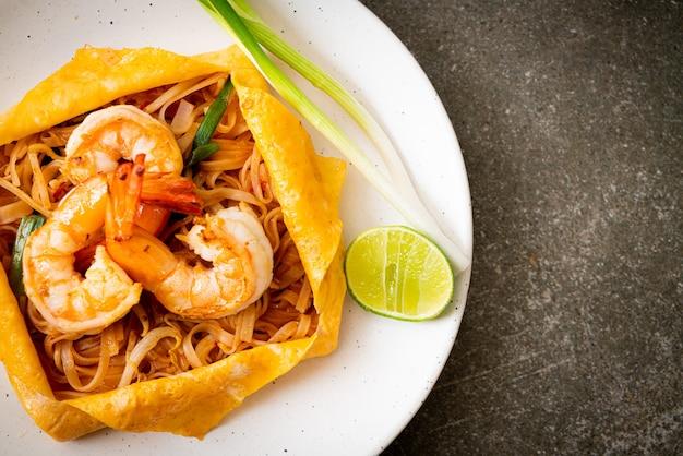 Thailändische gebratene nudeln mit garnelen und eierwickel (pad thai) - thai food style