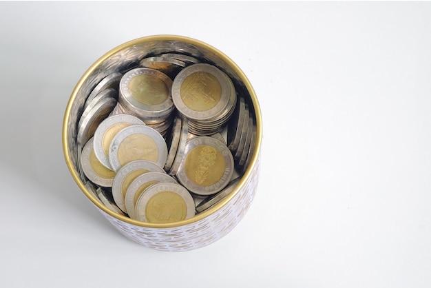 Thailändische geldmünze in der flasche, die für zukunft spart und investiert. draufsicht isoliert.