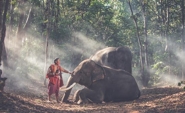 Thailändische hirten im dschungel mit elefanten. historische lifestyle-momente aus der thailändischen kultur