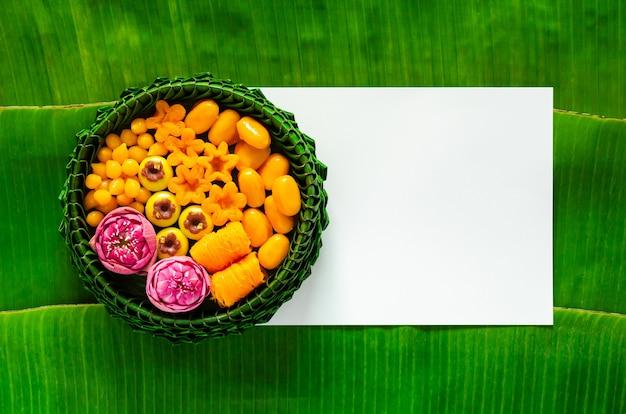 Thailändische hochzeitsdesserts auf bananenblattplatte oder krathong auf weißem leerem papier und bananenblatt