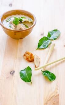 Thailändische hühnersuppe in der kokosmilch (tom kha gai) auf hölzernem hintergrund, thailändisches lebensmittel.