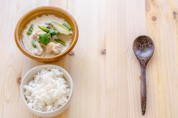 Thailändische hühnersuppe in der kokosmilch (tom kha gai) mit reis auf hölzernem hintergrund, thailändisches lebensmittel.