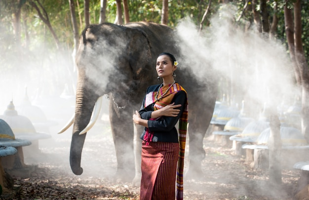 Thailändische junge frau im dschungel mit elefant
