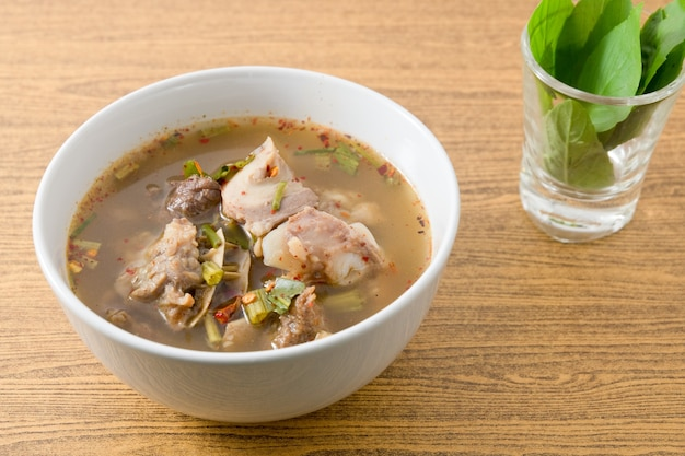 Thailändische klare würzige heiße und saure suppe der rindfleisch-entrails diente mit süßen basilsen.