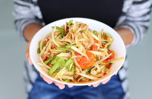 Thailändische küche der grünen papayasalat würzig köstlich in den frauenhänden