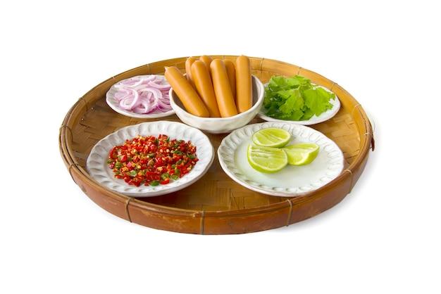 Thailändische küche zutat von würzigen salatschalotten der wurst, salari, zitrone, paprika, gesalzenes ei auf dreschendem bambuskorb