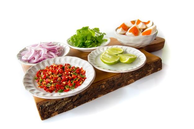 Thailändische küche zutat von würzigen schalotten des gesalzenen eies, salari, zitrone, paprika, gesalzenes ei auf dem hacken des holzes