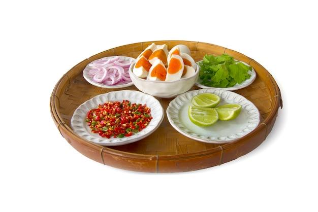 Thailändische küche zutat von würzigen schalotten des gesalzenen eies, salari, zitrone, paprika, gesalzenes ei auf dreschendem bambuskorb