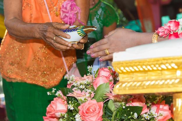 Thailändische kultur, hand einer braut, die weihwasser in der hochzeitszeremonie empfängt