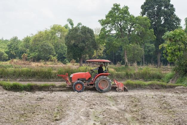 Thailändische landwirte bereiten mit einem traktor den boden für den reisanbau vor.