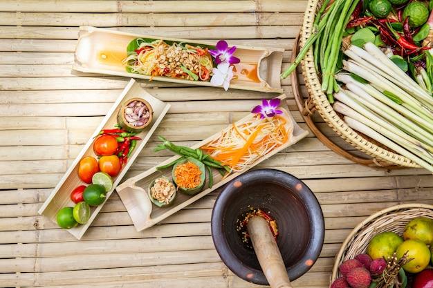 Thailändische lebensmittel papaya-salat-kochgeräte und papayasalat auf hölzernem brett