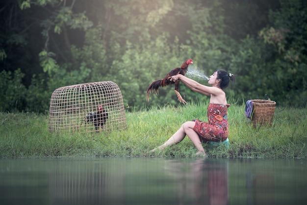 Thailändische lokale frauenleute mit dem hahnkämpfen