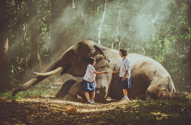 Thailändische mädchen, die nach der schule im dschungel nahe ihrem elefantenfreund spielen